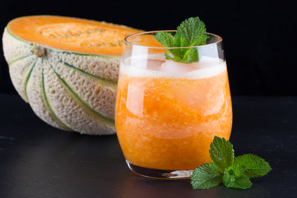 Fresh smoothie of melon on the black background